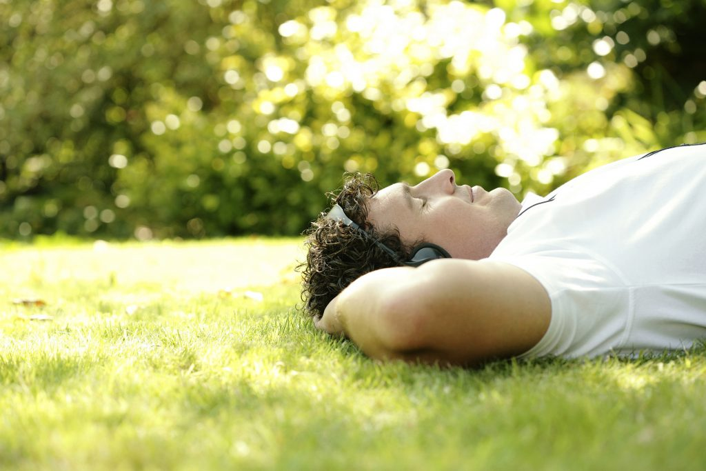 man relaxing with headphones on, laying in the grass