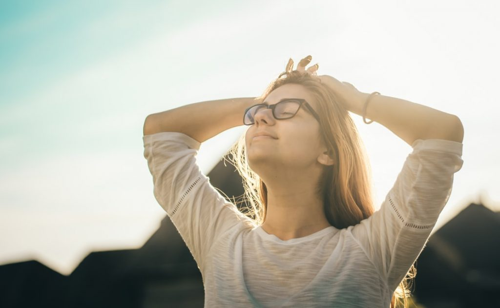 woman in sunshine, looking relieved