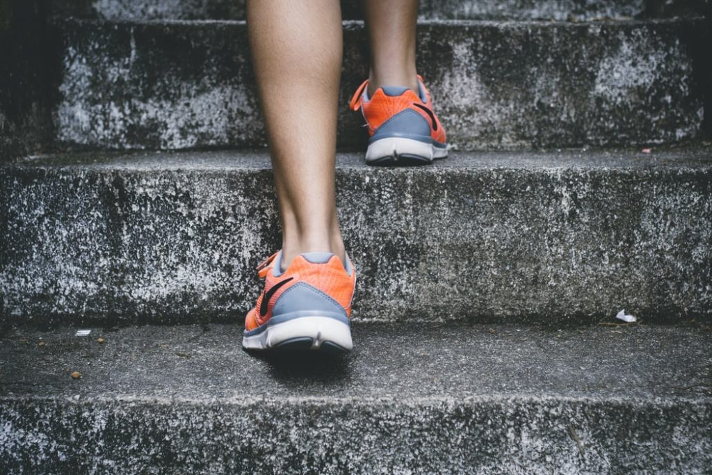 woman with orange running shoes going up stairs